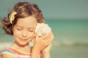 child lisenting to seashell